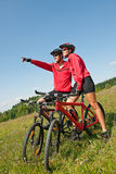 Summer bike - Young sportive couple in meadow. Sportive couple riding mountain bike in summer meadow on a sunny day Royalty Free Stock Image