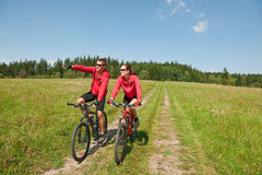 Summer bike - Young sportive couple in meadow. Sportive couple riding mountain bike in summer meadow on a sunny day Royalty Free Stock Photography