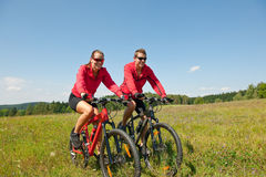 Summer bike - Young sportive couple in meadow. Sportive couple riding mountain bike in summer meadow on a sunny day Royalty Free Stock Photo
