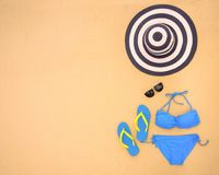 Summer bikini and accessories stylish beach set, Beach bikini summer outfit and sea sand as background, Top View, Concept.  stock photography
