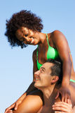 Summer bikini girl sitting on shoulders of man Royalty Free Stock Photos