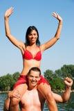 Summer bikini girl sitting on shoulders of man Stock Images