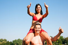 Summer bikini girl sitting on shoulders of man Royalty Free Stock Photo