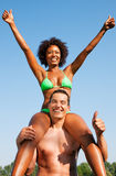 Summer bikini girl sitting on shoulders of man Stock Images