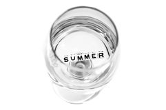 Summer blocks in glass water. Water filled in glass having floating summer letters. The objects are bright and isolated on white stock images