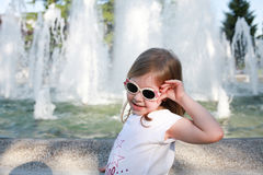 Summer blonde girl in the glasses near fontain Stock Image
