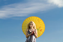 Summer blonde with yellow parasol. Smiling blonde girl with yellow parasol and blue sky. Copy space royalty free stock photo