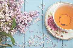 Summer blooming bouquet and a cup of black tea Royalty Free Stock Photos