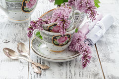 Summer blooming bouquet of lilac and china cup with black tea Royalty Free Stock Photography