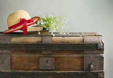 Summer blue flowers, old books and straw hat on vintage chest Royalty Free Stock Images