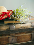 Summer blue flowers and straw hat on vintage chest Royalty Free Stock Photography