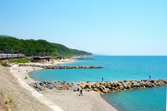 Sea shore breakwaters train sea sky sky mountains. Summer. Blue sea. Blue sky. The sun is shining. The shore of the sea with breakwaters made of huge stones Stock Images