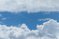 Summer blue sky. Fluffy clouds in a bright Summer blue sky stock image