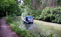 Summer boat trip. Boat trip down a peaceful canal shaded by trees on a hot summer day royalty free stock image