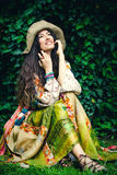 Summer boho fashion girl. Smiling young woman in silky boho style dress and  hat sit in garden summer day full body shot Royalty Free Stock Photography