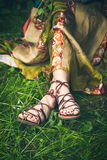 Summer boho fashion. Woman legs  on grass in strap flat sandals and boho style silky  dress  closeup Stock Photo
