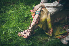Summer boho fashion. Woman legs  on grass in strap flat sandals and boho style silky  dress  with lot of bracelets on hands Royalty Free Stock Images