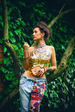 Summer boho  fashion woman. Young woman in blue embroidery jeans and golden glimmering top  in garden lean on tree Royalty Free Stock Images