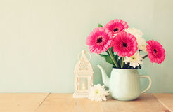 Summer  bouquet of flowers and lantern on the wooden table with mint background. vintage filtered image Royalty Free Stock Photo