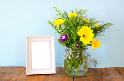 Summer bouquet of flowers next to blank vintage photography frame Stock Image