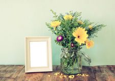 Summer bouquet of flowers next to blank vintage photography frame on the wooden table with mint background. vintage filtered image Stock Photo