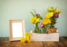 Summer bouquet of flowers next to blank vintage photography frame on the wooden table with mint background. vintage filtered image Royalty Free Stock Photography