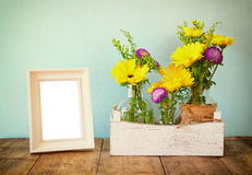 Summer bouquet of flowers next to blank vintage photography frame on the wooden table with mint background. vintage filtered image Royalty Free Stock Photo