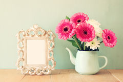 Summer bouquet of flowers and victorian frame on the wooden table with mint background. vintage filtered image Stock Photos