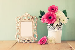 Summer bouquet of flowers and victorian frame on the wooden table with mint background. vintage filtered image.  stock images