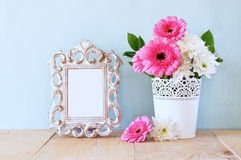 Summer bouquet of flowers and victorian frame on the wooden table with mint background. vintage filtered image Stock Photo