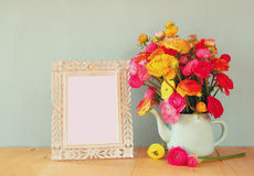 Summer bouquet of flowers and victorian frame on the wooden table with mint background. vintage filtered image Stock Images