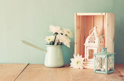 Summer bouquet of flowers and vintage lantern on wooden table with mint background. vintage filtered image Stock Photography