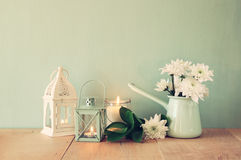 Summer bouquet of flowers and vintage lantern on the wooden table with mint background. vintage filtered image.  stock photography