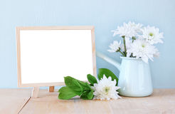 Summer bouquet of flowers on the wooden table and blackboard with room for text with mint background. vintage filtered image.  royalty free stock photo