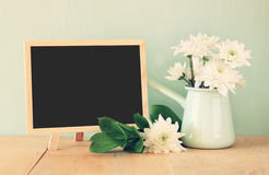 Summer bouquet of flowers on the wooden table and blackboard with room for text with mint background. vintage filtered image.  royalty free stock images