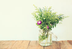 Summer bouquet of flowers on the wooden table with mint background. vintage filtered image.  stock photography