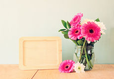 Summer bouquet of flowers on the wooden table and wooden board with room for text with mint background. vintage filtered image.  royalty free stock photography