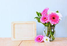 Summer bouquet of flowers on the wooden table and wooden board with room for text with mint background. vintage filtered image.  royalty free stock image
