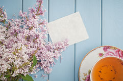 Summer bouquet of gentle blooming lilac with card and tea Stock Photography