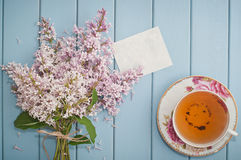 Summer bouquet of gentle blooming lilac with card and tea Stock Photos