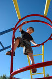 Summer Boy Climbing at Play. Boy climbing on the monkey bars against a blue sky Royalty Free Stock Images