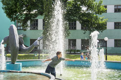 In the summer, boy play in the fountain in the park. Royalty Free Stock Images