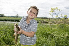 Summer boy stands near the lake and holding a big pike. Stock Images