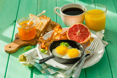 Summer breakfast - eggs, bacon, toast, jam, coffee, juice. Summer breakfast - eggs, bacon, toast, jam coffee juice copy space Royalty Free Stock Photo