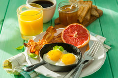 Summer breakfast - eggs, bacon, toast, jam, coffee, juice. Summer breakfast - eggs, bacon, toast, jam coffee juice copy space Stock Images