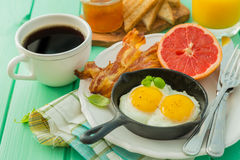 Summer breakfast - eggs, bacon, toast, jam, coffee, juice. Summer breakfast - eggs, bacon, toast, jam coffee juice copy space Royalty Free Stock Photography