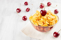 Summer breakfast with golden corn flakes, ripe cherries on white wood board. Decorative border with copy space. Royalty Free Stock Image