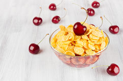 Summer breakfast with golden corn flakes, ripe cherries on white wood board. Decorative border with copy space. Stock Photos