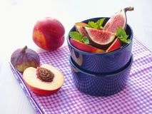 Summer breakfast. Ripe fruits with mint leaves and thyme sprig in violet vase. Fruit salad. Assorted summer fruits. Figs and peach. Es stock photography