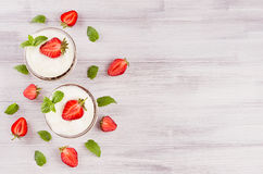 Summer breakfast with sliced strawberry, leaves mint  on white wood board, top view.  Decorative border with copy space. Royalty Free Stock Photography